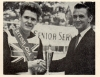 John Cobbin, the new 1962 Champion, receives the winners trophy from World Motor Cycle Speedway Champion Ronnie Moore(New Zealand).